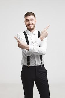 人、ビジネス、仕事、成功、キャリアのコンセプト。人差し指を反対方向に向けて興奮して笑っているトリミングされたひげを持つ感情的にポジティブな若い白人実業家の写真
