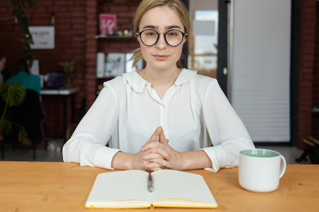 People, business, lifestyle and occupation concept. serious young female hr specialist wearing round eyeglasses and white blouse clasping hands during job interview, sitting at desk and making notes