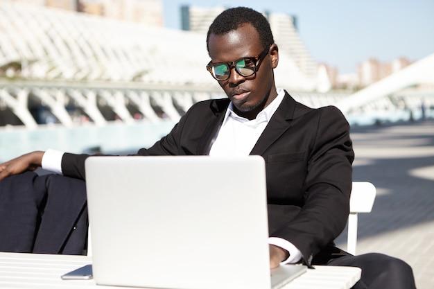 人、ビジネス、職業、技術の概念。ラップトップで正式にタイプするか、屋外のカフェテリアに座っている間にオンラインでニュースを読む服を着た眼鏡をかけた深刻な集中男性