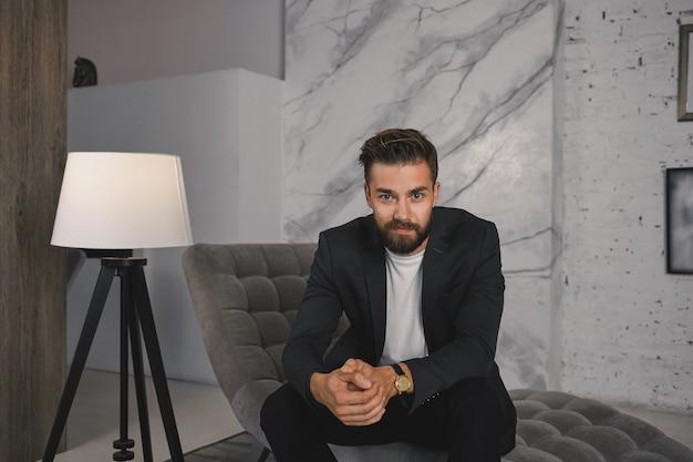 人、ビジネス、スタイル、そして贅沢なコンセプト。ソファの上のモダンで豪華なリビングルームでリラックスした高価な腕時計とエレガントなスーツを着て成功した若いヨーロッパのひげを生やした男の写真
