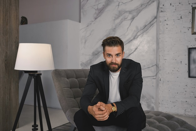 People, business, style and luxury concept. picture of successful young european bearded man wearing expensive wrist watch and elegant suit relaxing in modern luxurious living room on couch