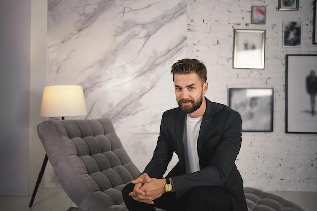 人、ビジネス、成功、ファッション、スタイルのコンセプト。ファッショナブルな成功した若いヨーロッパの男性起業家の肖像画、ファジーなひげがモダンなリビングルームに座って、腕時計とスーツを着て