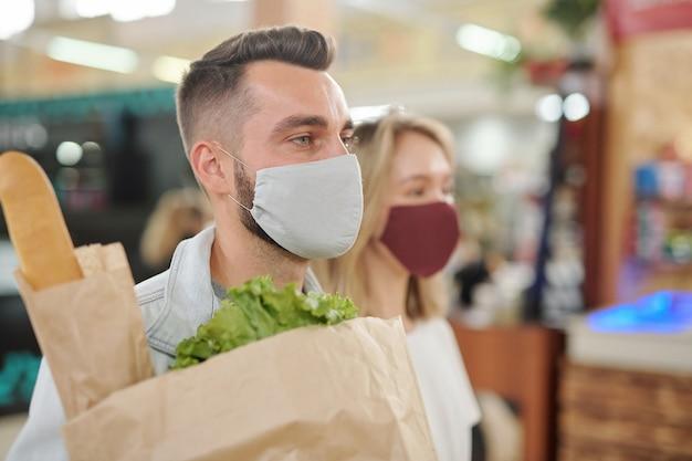 食品市場で商品を購入する人々は、果物と野菜のカウンターに焦点を当てています