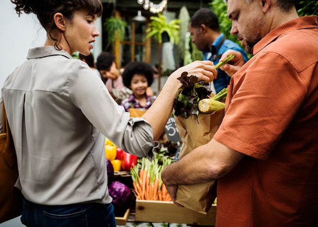 People buying vegetable from shop at market
