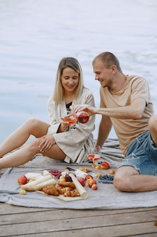 People by the river. delicious healthy summer picnic on the grass. fruits on a blancet.