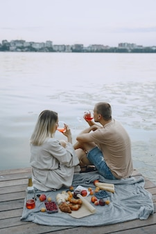 Persone in riva al fiume. delizioso picnic estivo sano sull'erba. frutta su un blancet.