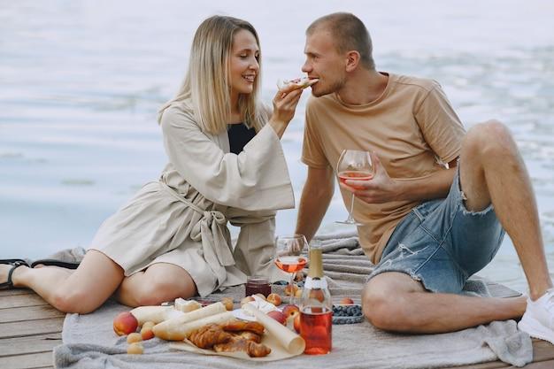 川沿いの人々。草の上でおいしい健康的な夏のピクニック。ブランセットの果物。