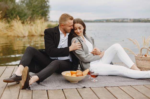 川沿いの人々。芝生の上でのおいしい健康的な夏のピクニック。ブランケットの果物。