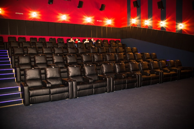 People came to the cinema and sit in soft leather chairs. premiere, people go to the cinema