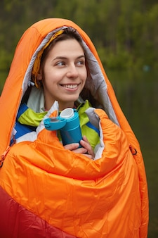 People and camping concept. glad lovely female hiker wrapped in orange sleeping bag, warms herself during cold day