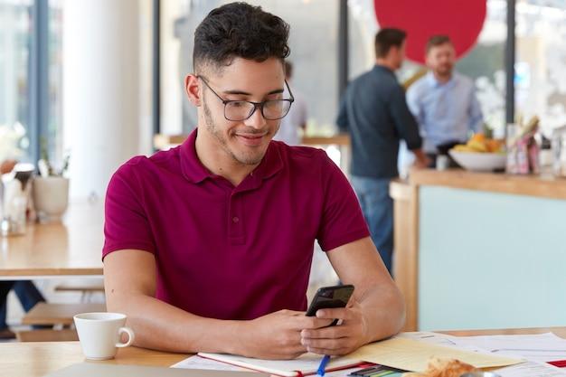 Люди, карьера, концепция технологии. красивый мужчина-хипстер в очках держит сотовую связь, наслаждается онлайн-общением, подключен к 4g, занимается оформлением документов в кафетерии, пьет ароматный кофе.
