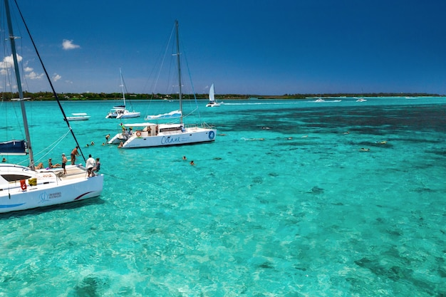 People on catamarans swim in a lagoon on the east coast of the island of mauritius in the indian ocean.
