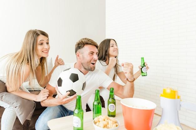 소파에서 축구를보고 목표를 축 하하는 사람들