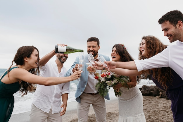 People celebrating with their friends getting married on the beach