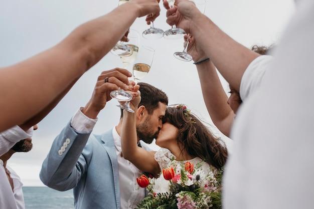 Persone che festeggiano con i loro amici che si sposano sulla spiaggia