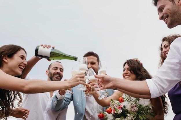 해변에서 결혼하는 친구들과 축하하는 사람들