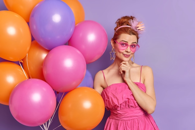 People celebration and holidays concept. fashionable nineties woman looks gladfully at camera wears clothes in vintage style prepares for party poses with balloons