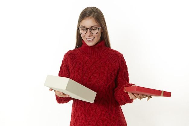 Persone, festa, gioia e felicità. gioiosa bella ragazza in occhiali e pullover caldo in piedi con la scatola aperta, guardando dentro con l'espressione facciale curiosa interessata, ricevendo un regalo per il compleanno