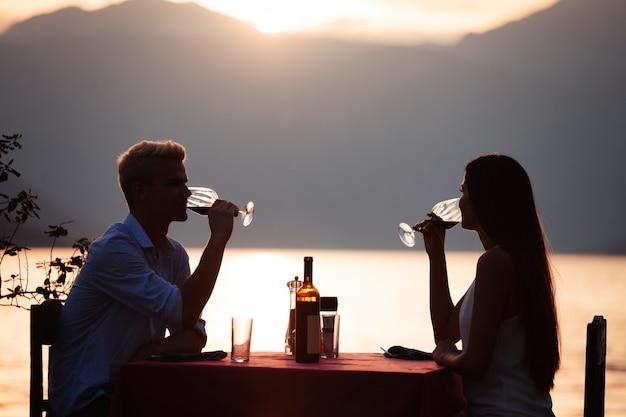 人、お祝い、休暇、新婚旅行、ロマンスのコンセプト。ビーチでロマンチックな夜のディナーを楽しんでいる若いカップル。