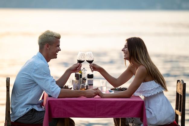 사람, 축하, 휴가, 신혼 여행 및 로맨스 개념. 해변에서 낭만적인 저녁 식사를 즐기는 젊은 부부.