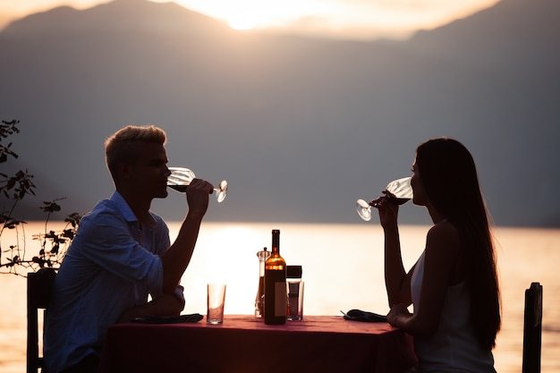 People, celebration, vacation, honeymoon and romance concept. young couple enjoying a romantic evening dinner on the beach.