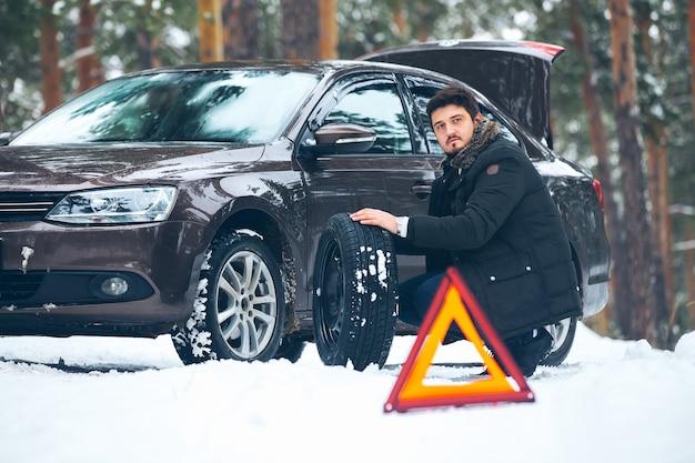 사람들은 겨울 숲에서 도로에서 깨진 차 후 바퀴를 바꿉니다.