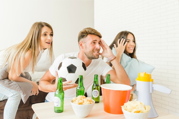 People cheering watching football match at home