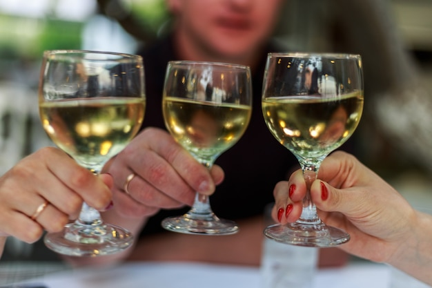 People cheering with white wine glasses