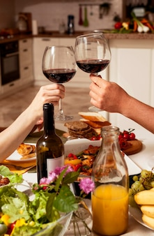 Люди, приветствующие с вином за обеденным столом