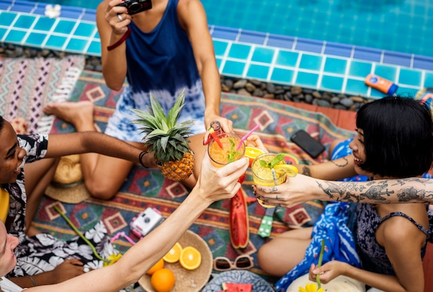 People cheers holding juice glasses by the pool summer time