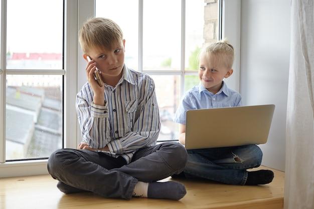 人、子供時代、現代のガジェット、ビジネスコンセプト。自宅で遊んでいる、ビジネスマンのふりをして、フォーマルな服を着て窓辺に座って、電子機器を使用している2人のかわいい白人の男の子