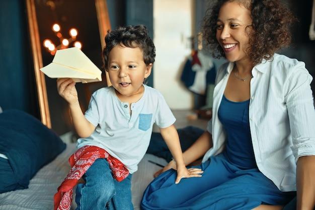 人、子供時代、子育て、家庭性の概念。幸せな若い混血の女性と家で楽しんでいる彼女のかわいい愛らしい幼い息子の肖像画