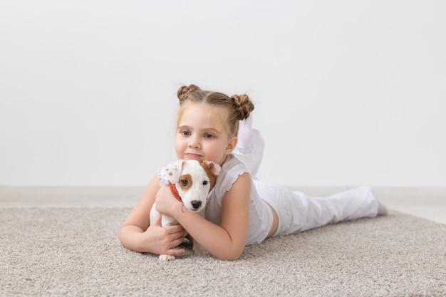 人、子供、ペットのコンセプト-かわいい子犬と一緒に床に横たわっている小さな子供の女の子。