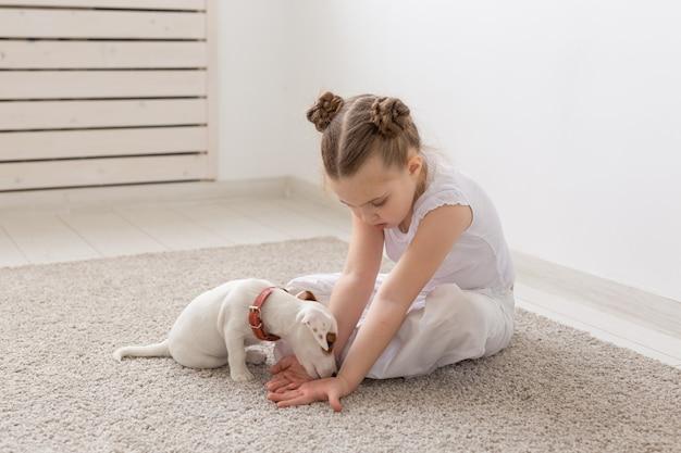 人、子供、ペットのコンセプト-かわいい子犬と一緒に床に座って遊んでいる小さな子供の女の子