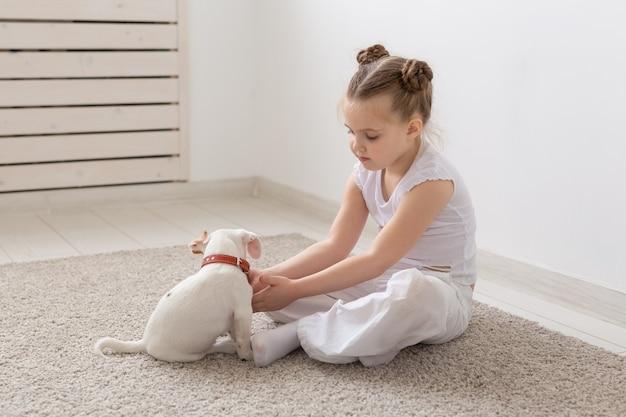 人、子供、ペットのコンセプト-かわいい子犬ジャックラッセルテリアと一緒に床に座って遊んでいる小さな子供の女の子