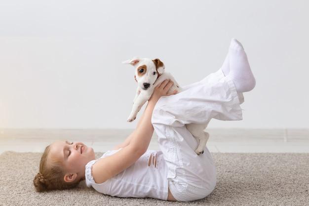人、子供、ペットのコンセプト-かわいい子犬ジャックラッセルテリアと一緒に床に横たわっている小さな子供の女の子