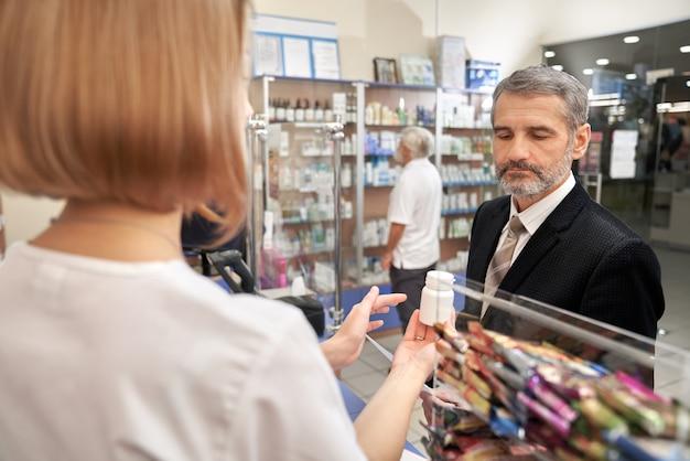 Люди выбирают, покупая лекарства в аптеке.