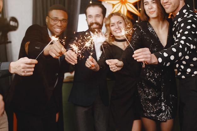 Persone in una decorazione christman. uomo in abito nero. celebrazioni di gruppo capodanno. persone con luci bengala.