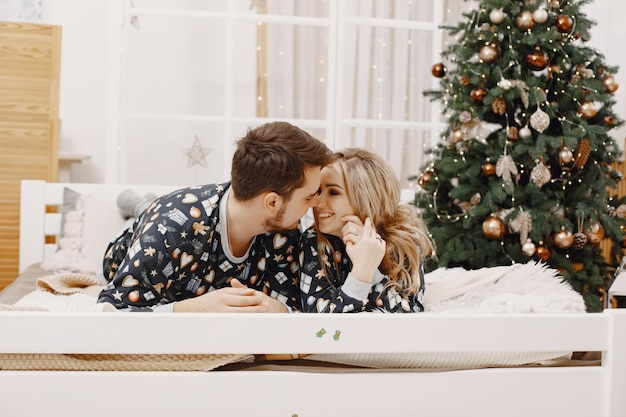 People in a christman decorations. man and woman in a identifical pajamas. family on a bed.