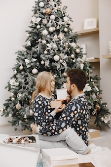 People in a christman decorations. man and woman in a identifical pajamas. family at home.