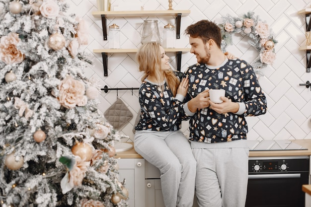 People in a christman decorations. man and woman in a identifical pajamas. family in a kitchen.