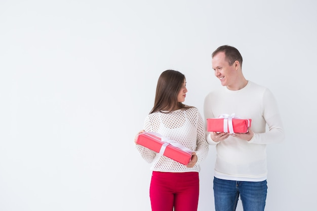人々、クリスマス、誕生日、休日、バレンタインデーのコンセプト – 幸せな若い男女が、白い背景にコピースペースを持つギフトボックスを持つ。
