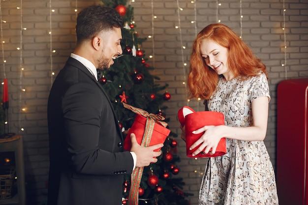 Persone in decorazioni natalizie. uomo in abito nero. donna con scatola rossa.