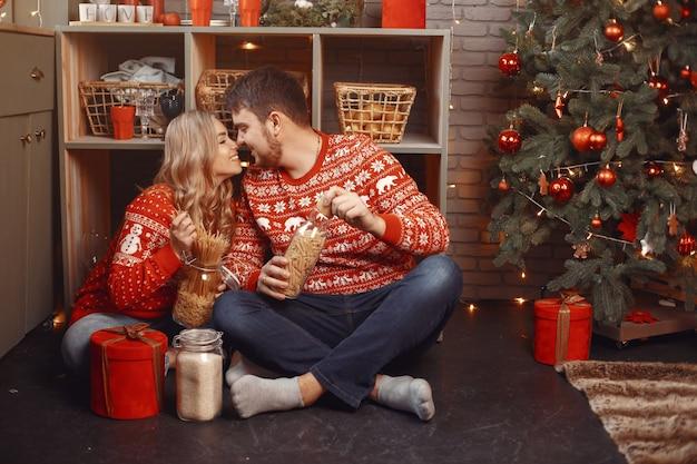 Persone in un addobbo natalizio. uomo e donna in un maglione rosso.