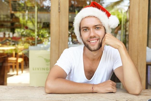 사람, 크리스마스, 새해 및 휴일 개념. 유쾌 하 게 웃 고 산타 클로스 모자를 쓰고 세련 된 수염과 매력적인 젊은 hipster의 얼굴 만