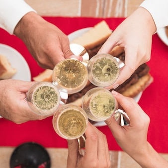 People clanging champagne glasses at festive table