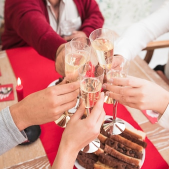 People clanging glasses of champagne at festive table