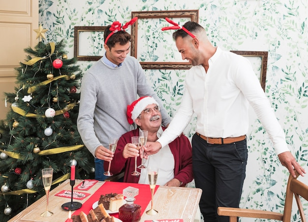 People clanging glasses of champagne near festive table