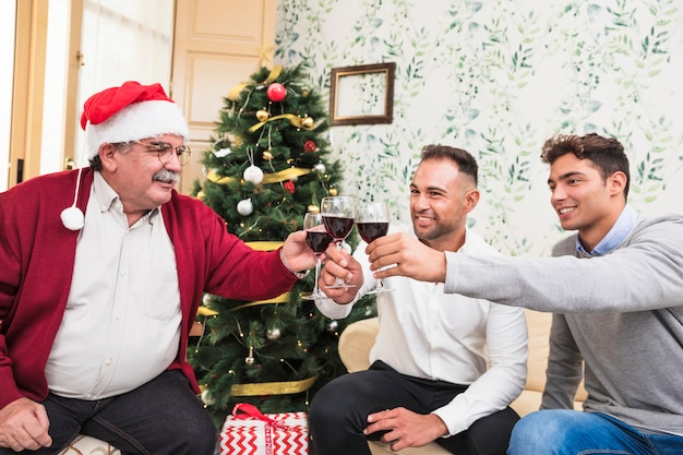 People clanging glasses near christmas tree