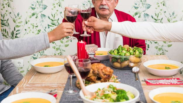 People clanging wine glasses at festive table